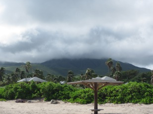 Beach palapas, and Nevis Peak, shrouded in clouds.