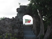 Sugar mill ruins framing the flag.